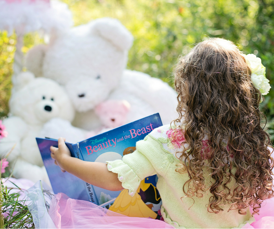 girls sits reading to her teddies - one way to boost children's vocabulary