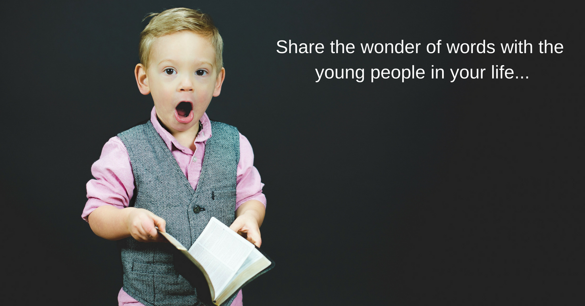 young boy open-mouthed in wonder at the book in his hand