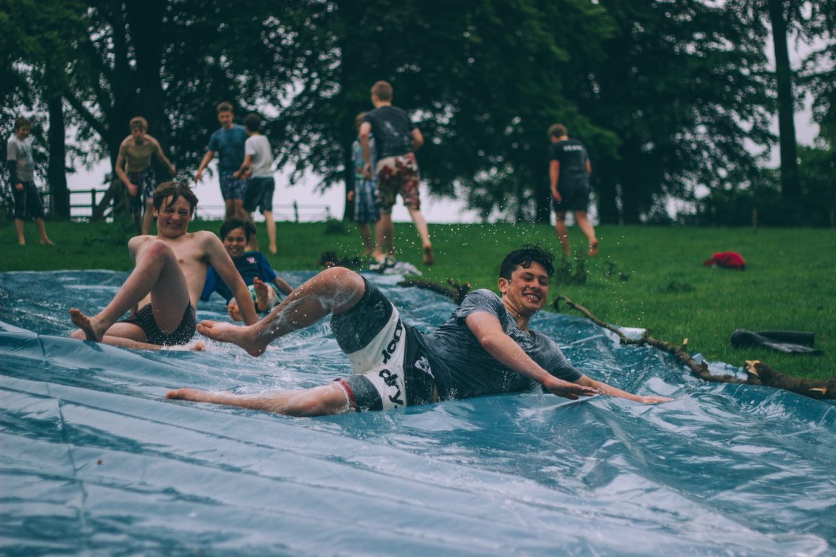 summer holiday fun with boys sliding along plastic sheet